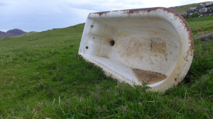 an old white partially rusted bathtub on its side on a grassy hill