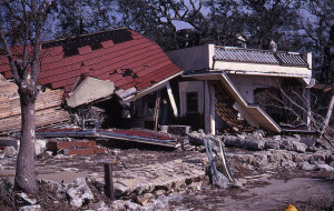 color photo of a building damaged by Camille with walls on the ground, signs down, and a partially collapse and holey roof