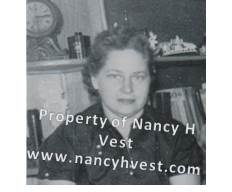 B&W photo of a 40-ish woman with short dark hair. She is wearing a dark colored blouse.