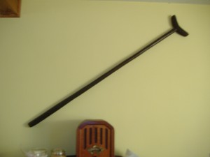 Photo of a simple crutch that is hanging on a wall.