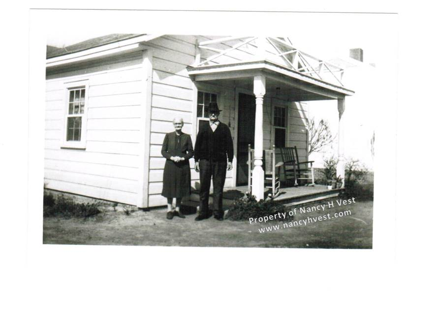 B&W photo of an elderly couple in front of a small white house with a little porch with 2 rocking chairs. 1940s.