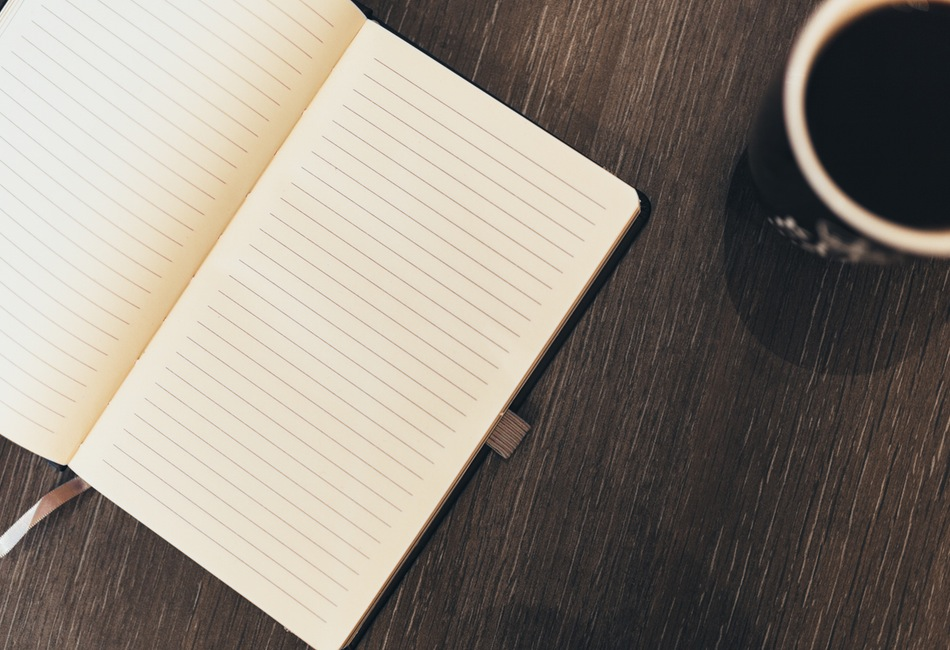 Opened journal with cup of coffee on a brown table.