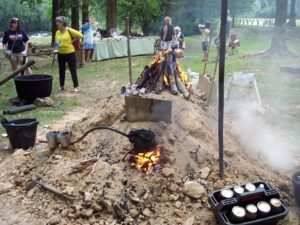 A dirt mound with 2 fires set up to show how what a turpentine farmer does with the tree sap.