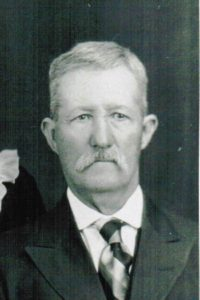 B&W photo of an older man with grey/white hair and a grey/white mustache. He is wearing a dark suit, white shirt, and multi-colored tie.