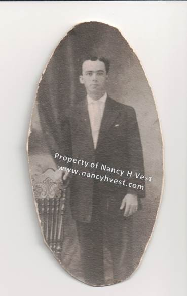 B&W of a young man in a dark suit and white shirt. He has one hand on the back of a chair. He is clean-shaven and has short, wavy dark hair. No smile. Early 1910's.