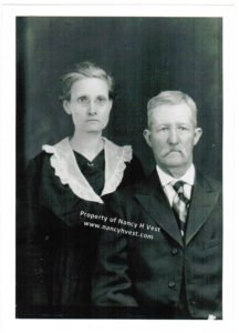 B&W photo of an upper middle-age couple from the waist up. Woman in dark dress and white lace collar, graying hair pulled up, and wearing glasses. Man in dark suit with checkered tie and white shirt, gray mustache and hair. Neither is smiling.