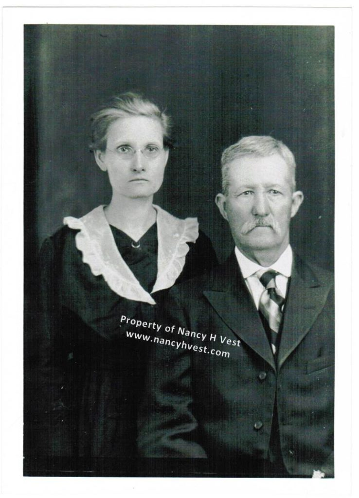 B&W photo of upper middle-aged couple, woman in black dress with white collar, wearing glasses, graying hair pulled up; man in dark suit with plaid tie, short gray hair and mustache.