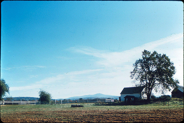 Farm house, plowed field, white fence, blue sky, mountains in distance