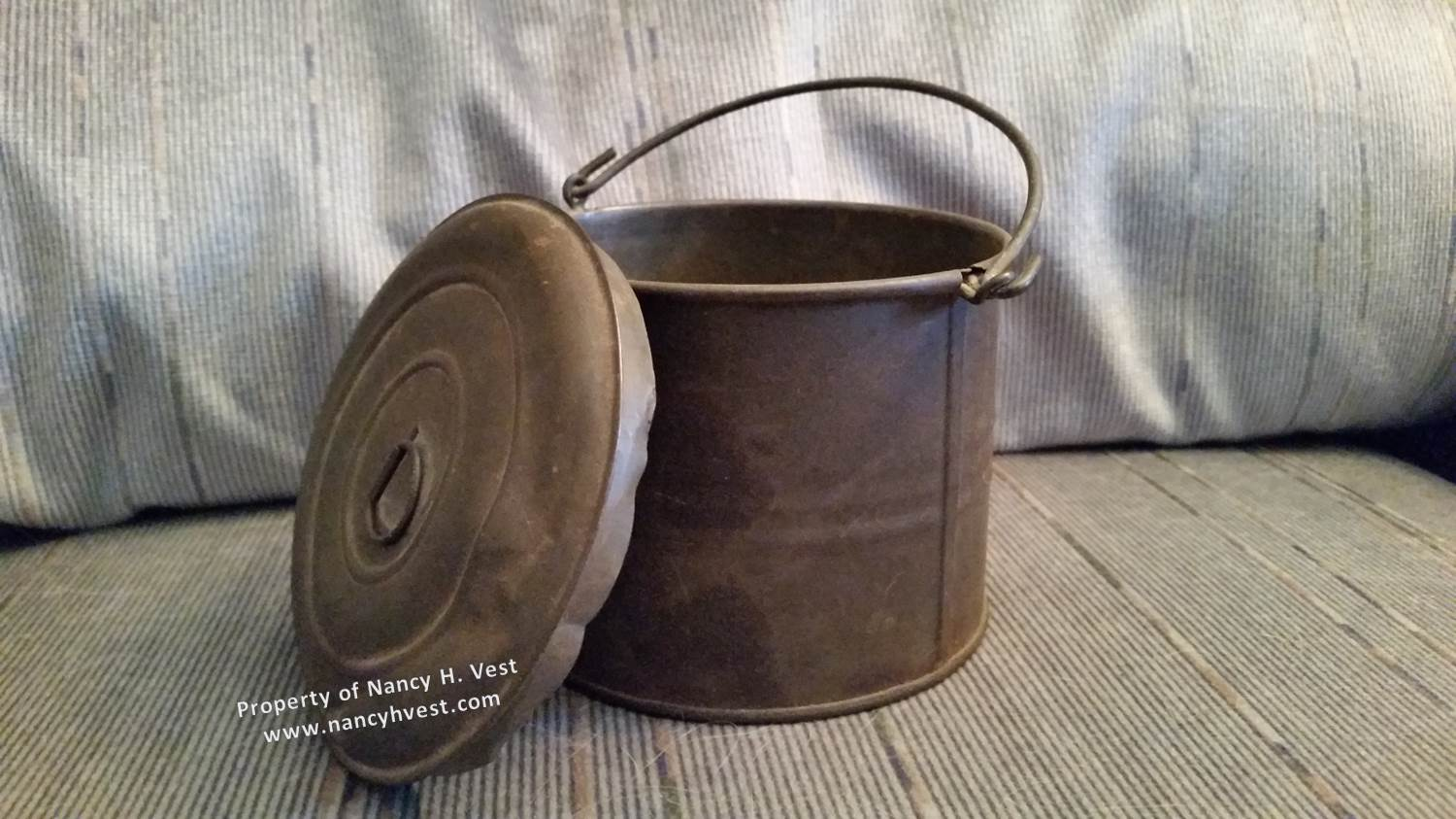 A small circular metal tin carried by my maternal grandfather Daniel Martin; the tin is about 3.5 inches tall and 4 inches diameter, with a removable lid and a carrying handle like bucket's typically have.