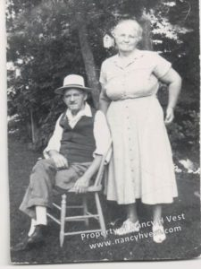 B&W photo of two near senior citizens. Man sitting in chair wearing a white hat, shirt and socks; dark sweater vest, pants and shoes. Woman standing, wearing light colored dress and shoes. Graying hair pulled back.