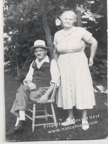 My maternal grandparents, Daniel and Florrie Martin, in their 60's;Dan is sitting in a wooden kitchen chair with his legs crossed and Florrie is standing behind him.