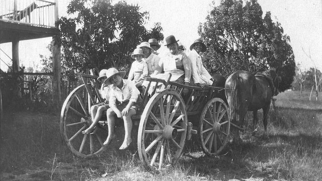 B&W photo of a horse drawn wagon with several people in the wagon, dressed as if going visiting or to church. Everyone is wearing a hat of some kind.