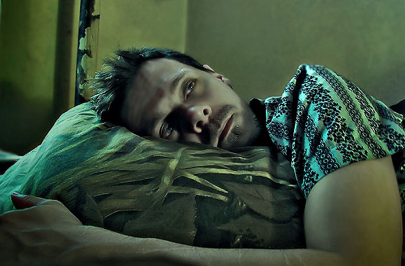 Young man laying on his side with head on pillow, looking tired but unable to sleep; the look of someone with insomnia.