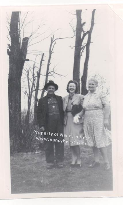 Black and white photo of older middle aged couple with their 20-something daughter. Man in dark overalls; and dark hat, jacket and boots. Daughter in a light colored dress and jacket with dark shoes, holding a black purse and white gloves. She has short dark hair. Older woman in light colored patterned dress, wearing dark shoes. Her gray hair is pulled up. All are smiling.