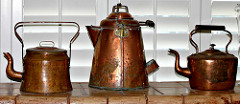 Three vintage copper coffee pots lined up side by side, tow with curved handles on top and one with curved handle on the side.