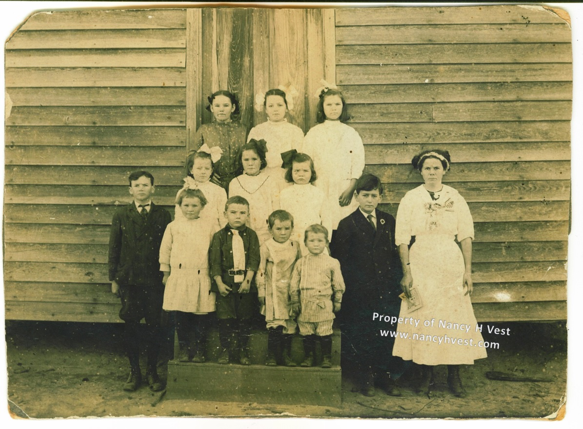 Circa 1912 B&W school photo of 12 elementary aged students and teacher, children arranged in 3 rows standing on the school steps and all in their best clothes.