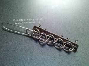 Color photo of a Devil's Knot puzzle made from metal. It has nails and rings and bent metal pieces.