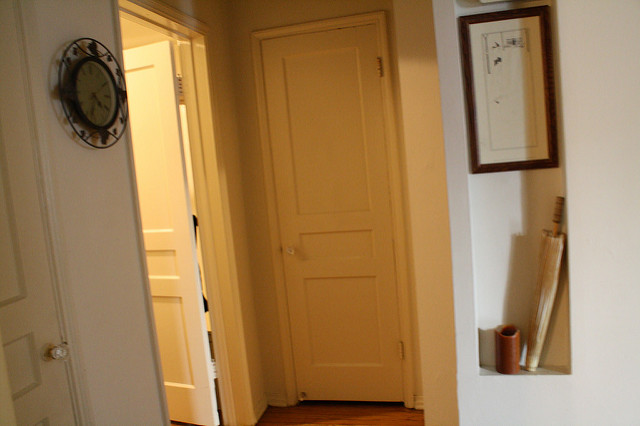 Hallway of an old house; color photo showing 3 doors one of which is opened. The closed doors are painted yellow.