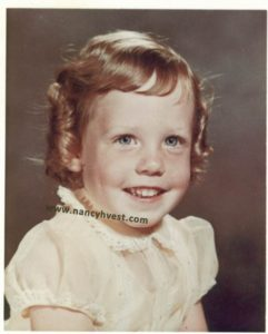 smiling girl about 3 years old, with pale skin and freckles, dirty blond hair set in ringlets, and wearing a pale yellow dress.