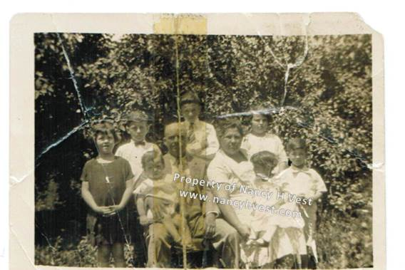 B&W photo from 1929 of a middle-aged couple seated outside with their children around them for a family photo. They appear to be dressed in their best clothes.