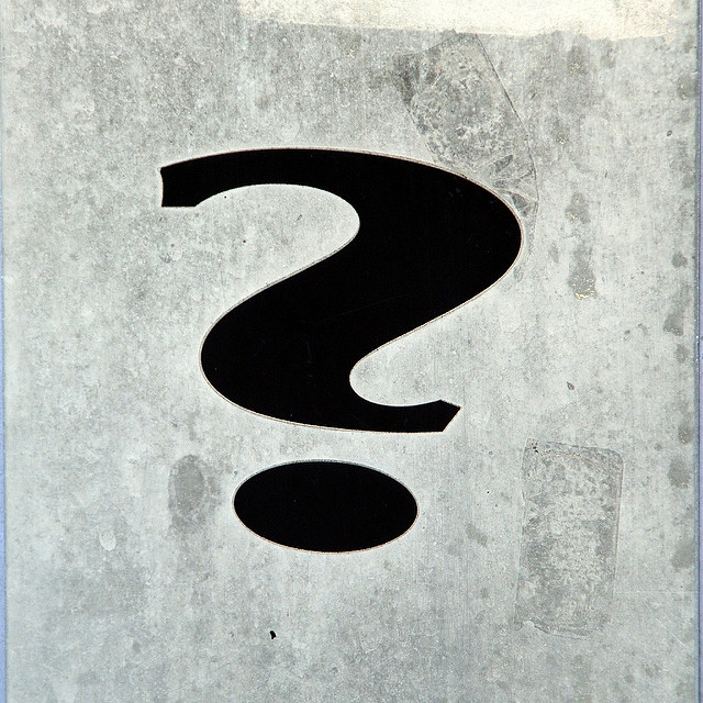 large black hand drawn question mark on a speckly gray background