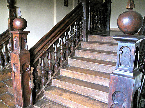Color photo of a bare wood staircase with scrolled spindles and carved end pieces.