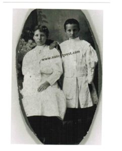 B&W photo of two girls in long-sleeved white dresses, one seated and one standing.