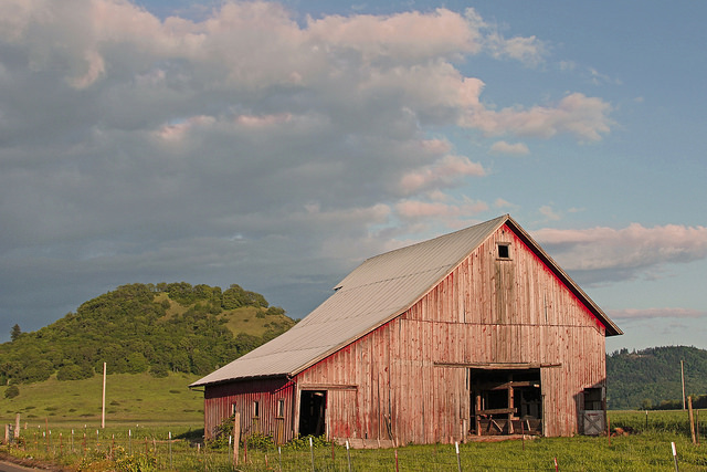 A old red barn against the backdrop of a partly cloudy sky with pinkish clouds.