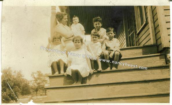 B&W photo of a 1926 farm wife and her 6 children sitting at the top of a steep exterior staircase.
