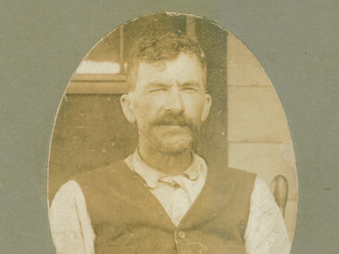 B&W bust photo of a man wearing a light shirt and a dark vest. Man has short, dark, wavy hair and a thick dark mustache.
