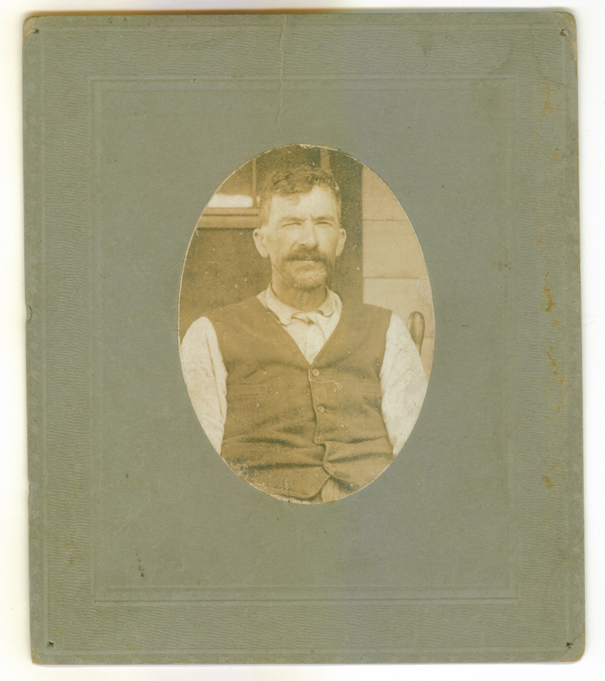 B&W photo of a middle aged man with short dark hair and a dark mustache, wearing a white long sleeved shirt and a dark vest, sitting in a chair.