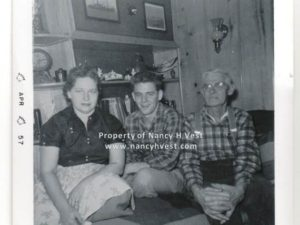 B&W photo of three. Woman wearing a dark shirt and a light colored skirt, short brown hair. Man in middle in early 20's wearing a plaid shirt and light colored pants. Short dark hair. Man on right is white haired elderly man wearing a plaid shirt and dark pants.