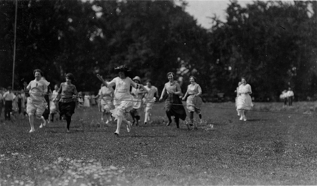 B&W photo of men and women participating in a foot race in 1920