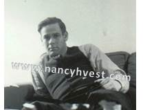 B&W of a mid 20's man wearing a long sleeved white shirt and a dark vest. He has medium dark hair and is clean-shaven.