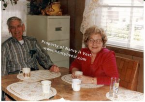 color photo of two late middle-aged people. A man wearing a plaid shirt, and a woman wearing a red shirt. Both smiling. Man has gray hair. Woman is dark blond. Sitting at a kitchen table, both have coffee cups.