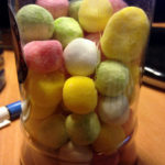 clear glass cylinder jar with homemade bonbons in a variety of pastel colors