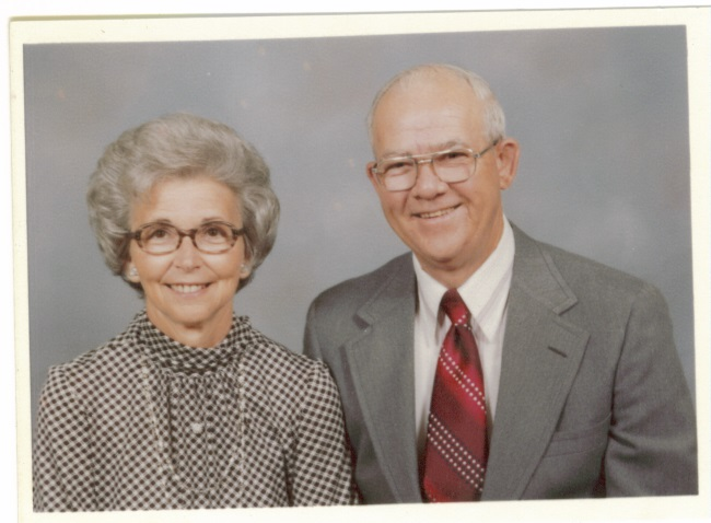 color photo of a smiling middle aged couple; woman in a grey checked dress, short curled grey hair and thin black-framed glasses; man in a grey suit with a dark red tie and a white shirt, balding head with white hair, and silver framed glasses