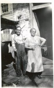 B&W photo of an elderly couple standing outside a brick and wood building. The woman is short, wearing a light colored blouse and mid-calf skirt and black shoes with her gray hair pulled back in a bun, and she has glasses on. The man is clearly bent over and uses a cane. He is wearing a white shirt, dark pants, and dark suspenders and shoes. His hair is brown and he has a receding hairline and a salt-n-pepper full beard and mustache.