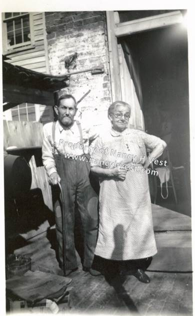 B&W photo of an elderly couple with an open back door behind them. Man is hunched over and holding a cane, wearing a pale long -sleeved shirt and dark pants with suspenders and dark shoes. He has dark hair. Woman has grey hair, wears glasses, wearing a light colored blouse and mid-calf skirt and dark shoes.