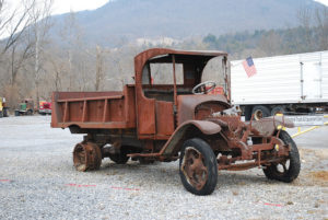 Color photo of a rusted 1920's era truck. Some of the engine cover is missing, as is one of the back tires.