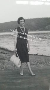 B&W photo of an upper middle aged woman in a back sleeveless dress, cream colored pumps, a faux pearl necklace, and carrying a large white handbag. She is front of a lake. Her hair is short, brown, and curled.