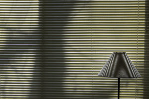 color photo of large Venetian blinds, closed and with shadows of a tree and branches coming from the outside, and a lamp in front of the blinds