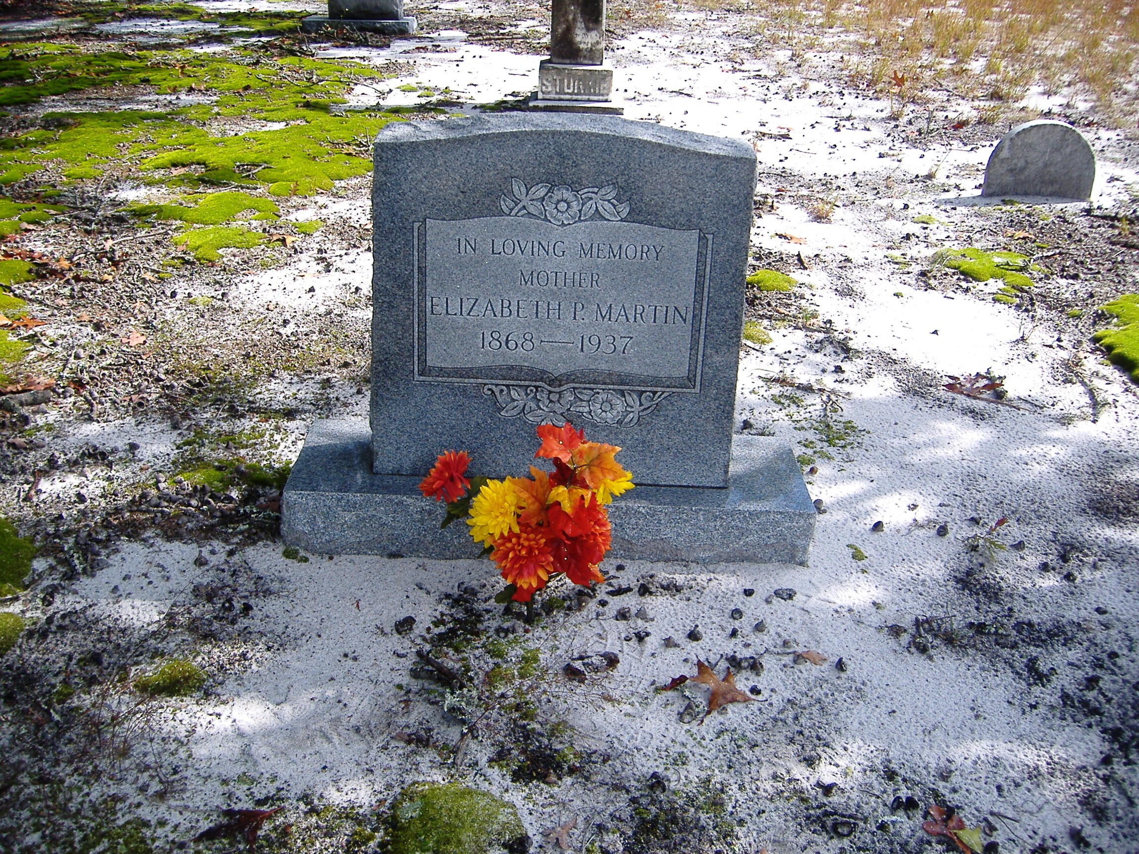 color photo of an upright marble headstone with red and orange flowers on the ground in front of it