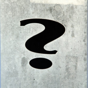 A thick black question mark on a dappled gray background.