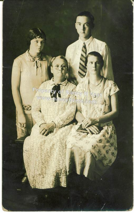 B&W professional photo of 4 people. Seated late 50's mother in long white dress and wearing glasses; seated early 30's woman with dark hair in a long flowered dress; standing young woman in a mid-calf dress and short dark hair; standing young man in white shirt, striped tie, short dark hair.