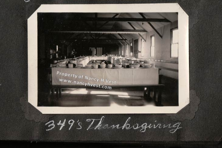 B&W photo of a mess hall with tables set with tablecloths and nice dishes