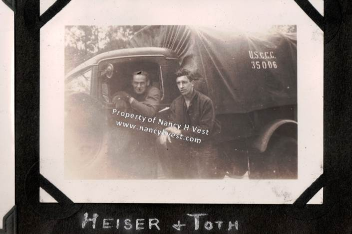 B&W photo of two mid-20's men, on sitting in truck and one outside army-like truck. Both men in uniform, clean shaven, and short hair.