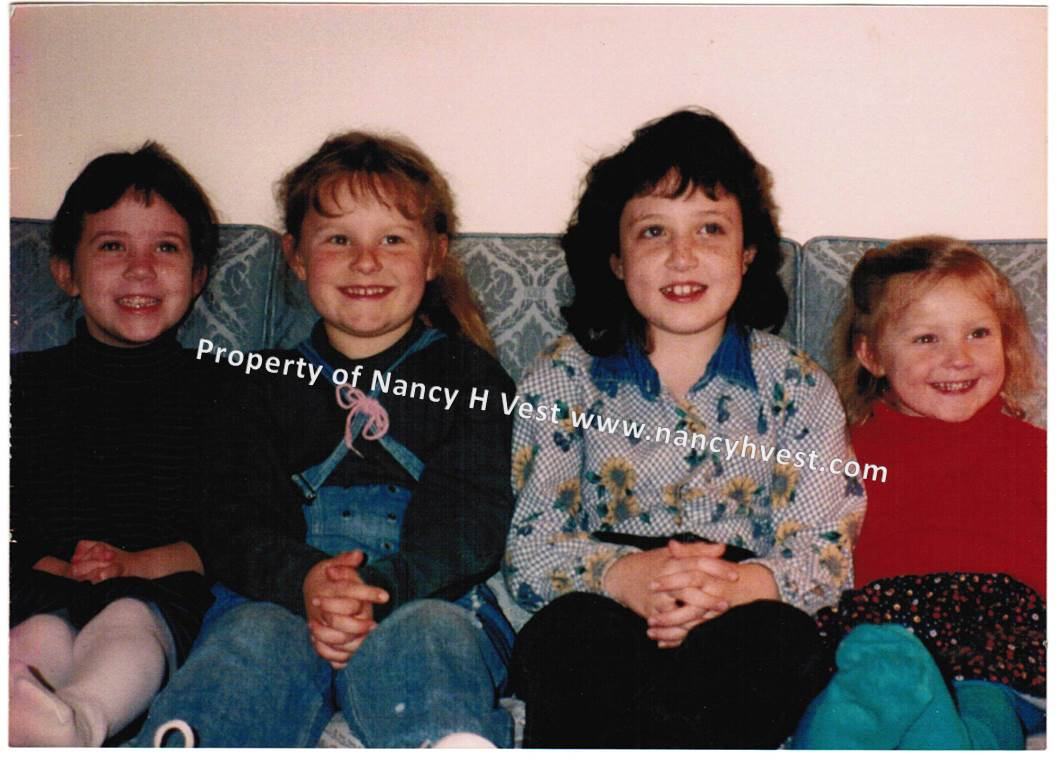 Color photo of 4 girls (ages 3-8).2 blondes, 2 brunettes, dressed casually. All smiling.