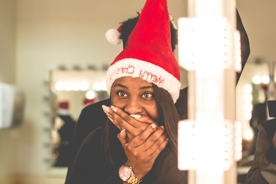 Color photo of young woman of African descent wearing a red and white Merry Christmas hat with her hand to her mouth like she is surprised by something.