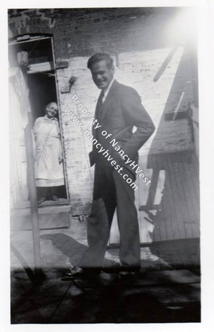 B&W of a mid 20's man in the 1930's wearing a dark suit and black dress shies, standing sideways with his hands in his pockets. The man is smiling broadly, and he has dark short hair and a ruddy complexion.An elderly woman stands in the doorway in the background. She is wearing a light colored dress with a long white apron over it and dark shoes. Her gray hair is pulled up, and she wears glasses.